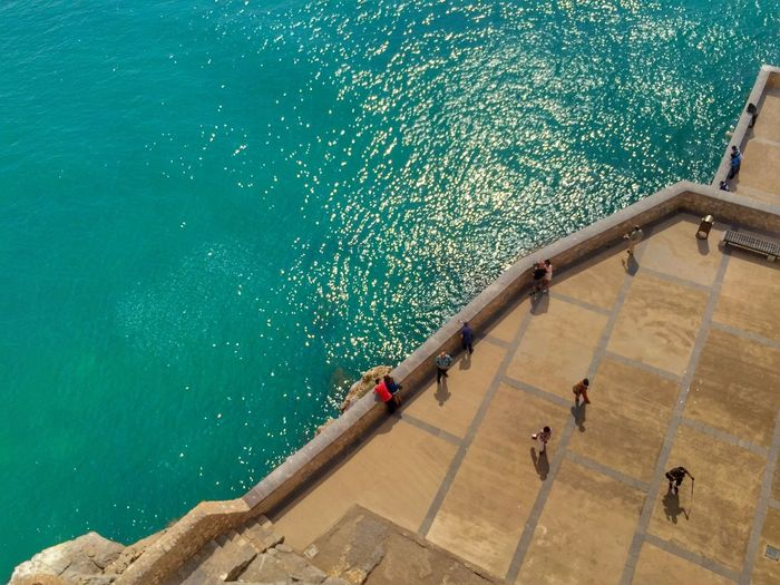 High angle view of people on building terrace by sea