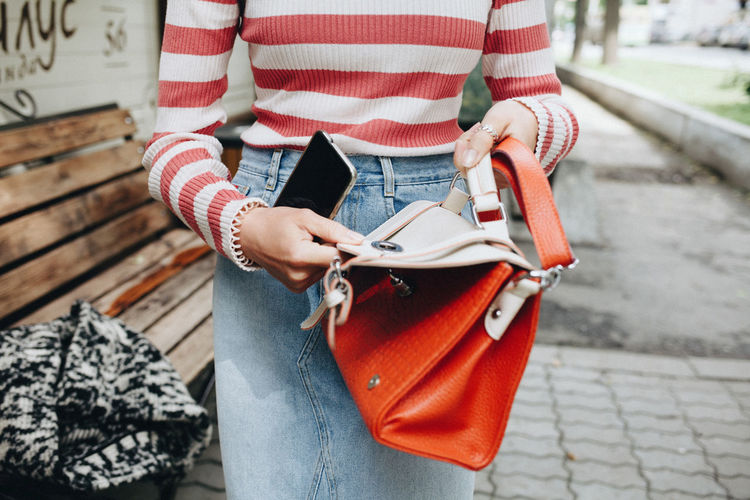 Woman holding a bag Adult Adults Only Casual Clothing Close-up Day Holding Human Hand Lifestyles Low Section Men Midsection Mobile One Person Outdoors People Purse Real People Standing Striped Women Young Adult