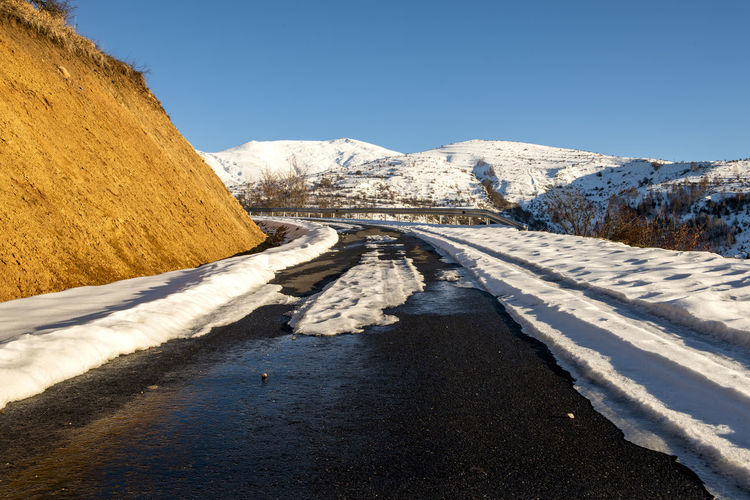 Road amidst snowcapped mountains against clear sky