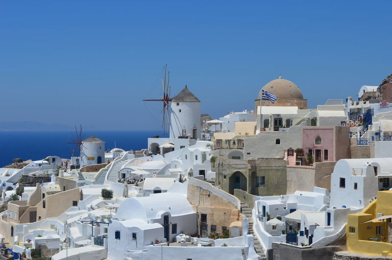 Traditional windmill in town at santorini against clear blue sky