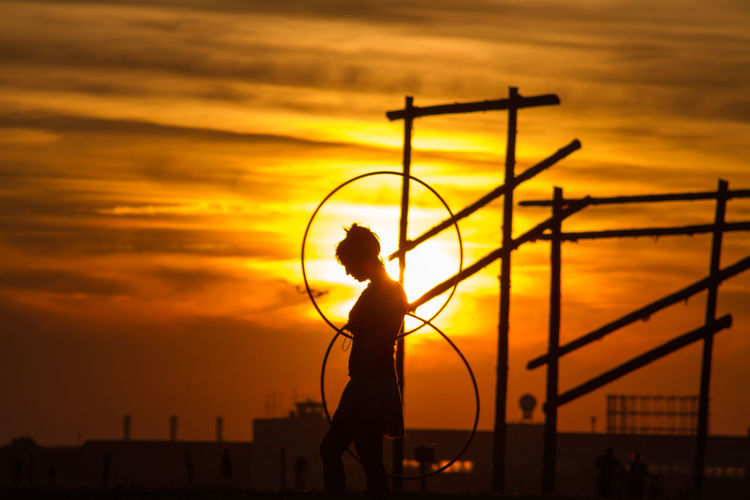 Silhouette woman with plastic hoop during sunset