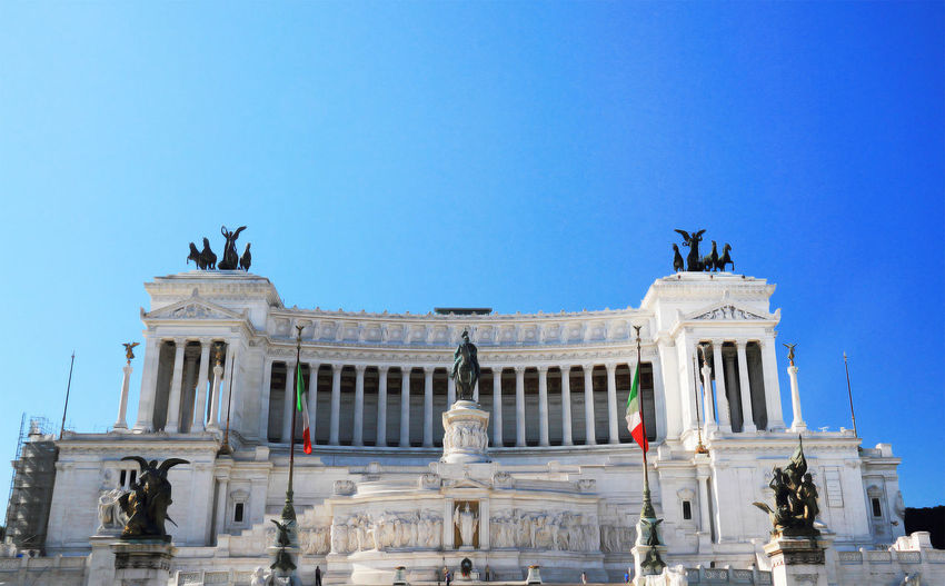 Low angle view of altare della patria against clear blue sky in city