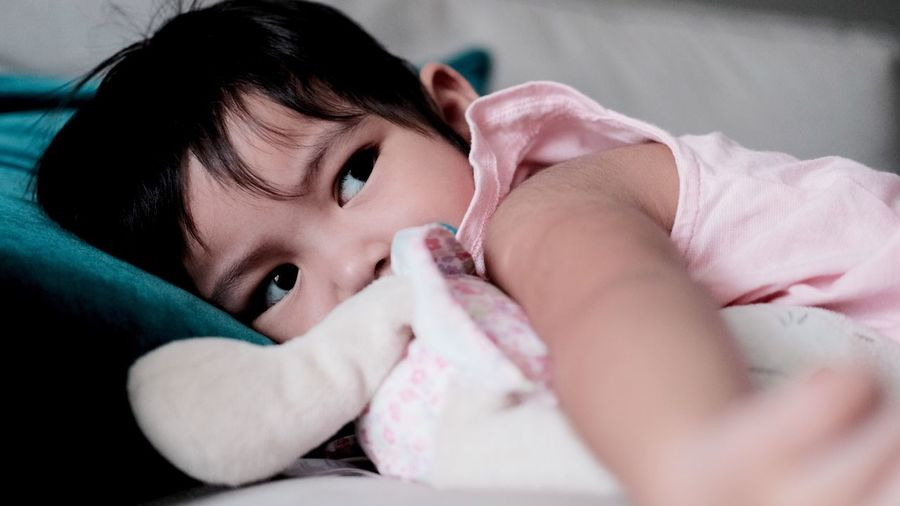 Close-up of baby girl lying on bed at home