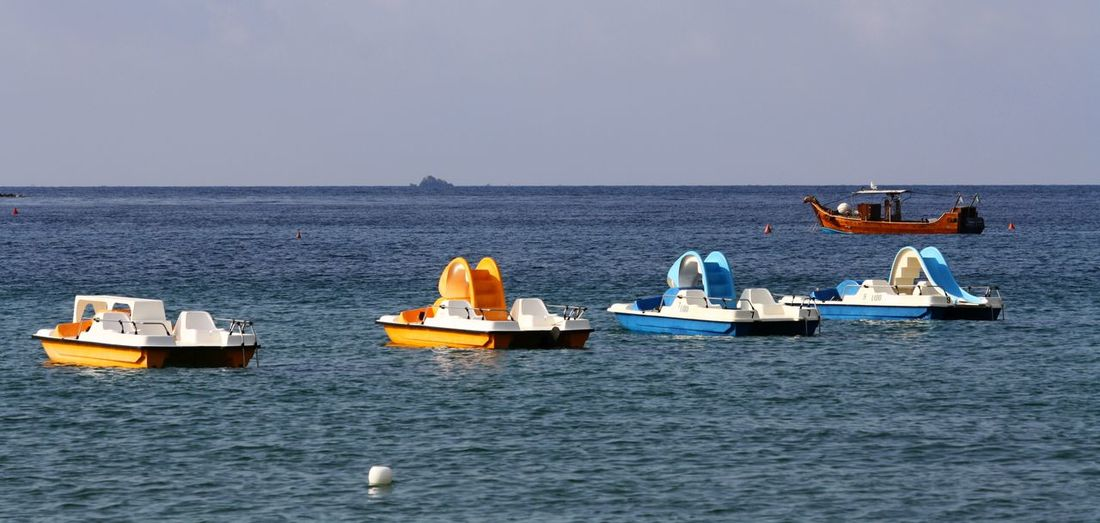Empty boats moored on sea against sky