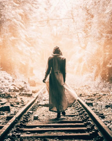 Rear View Full Length Of A Woman Walking On Railway Tracks