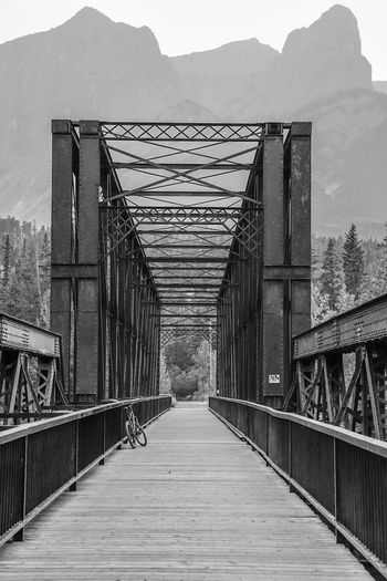 where is the bicyclist? Water Blackandwhite Monochrome River Bike Mountain City Gate Sky Architecture Built Structure Wrought Iron Footbridge Iron Arch Bridge Bridge - Man Made Structure Iron - Metal Steps Bridge