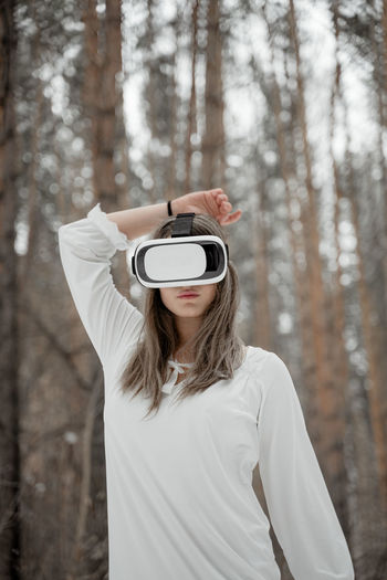 Woman wearing virtual reality simulator against trees outdoors