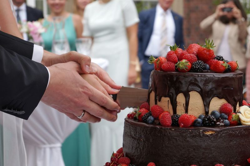 Cropped Image Of Bride And Groom Cutting Cake During Wedding