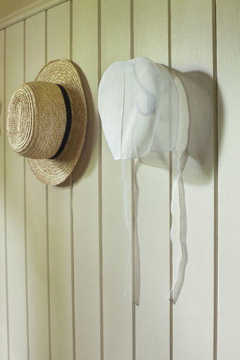 Amish straw hat and organdy bonnet hang on a wall Amish Black Bonnet Color Hat Hooks No People Organdy Religion Ribbon Straps Straw Wall White Wood