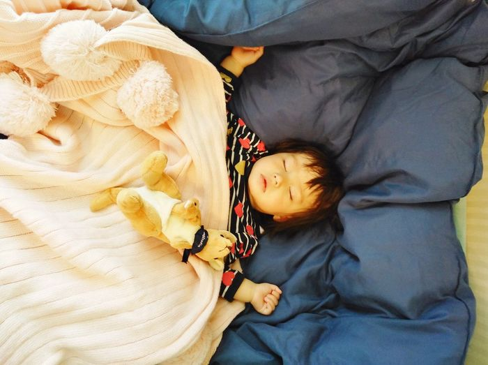 Directly above shot of girl sleeping on bed