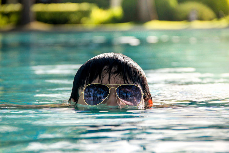 High Section Of Person Wearing Sunglasses While Swimming In Lake