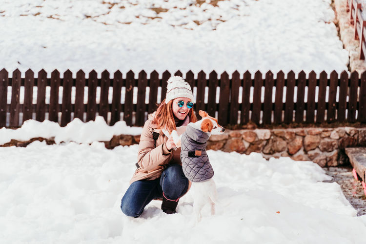 Full length of woman with dog wearing knit hat crouching on snow outdoors