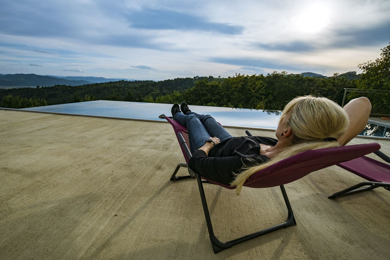 Woman sitting on deck chair by infinity pool against sky