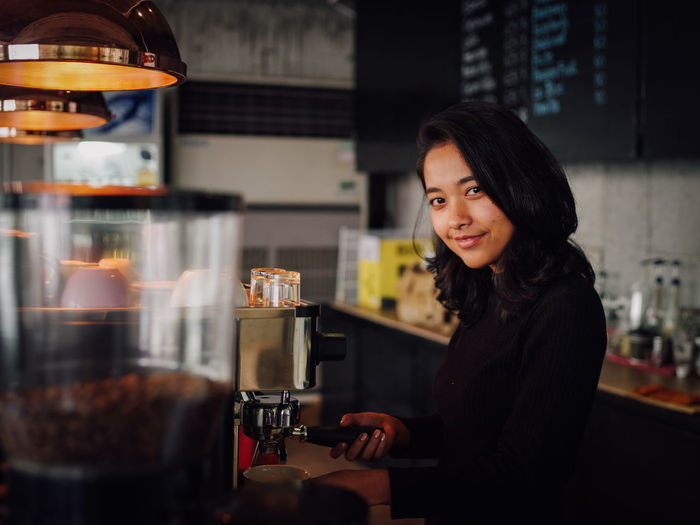 Adult Barista Business Cafe Coffee Maker Coffee Shop Drink Food And Drink Hair Hairstyle Indoors  Lifestyles Mid Adult One Person Preparation  Real People Refreshment Selective Focus Waist Up Women Young Adult Young Women