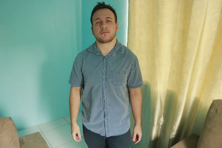 Blue Eyes One Person Indoors  Front View Standing Young Adult Casual Clothing Young Men Three Quarter Length Looking At Camera Lifestyles Leisure Activity Real People Home Interior Looking Wall - Building Feature Curtain Portrait Contemplation Turquoise Colored