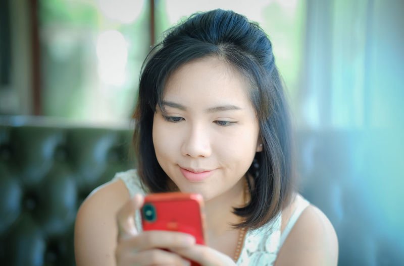 young asian woman use smartphone, thailand girl Headshot One Person Portrait Holding Wireless Technology Real People Portable Information Device Front View Mobile Phone Young Adult Technology Lifestyles Smart Phone Women Using Phone Looking Focus On Foreground Young Women Leisure Activity Hair Beautiful Woman Hairstyle Outdoors