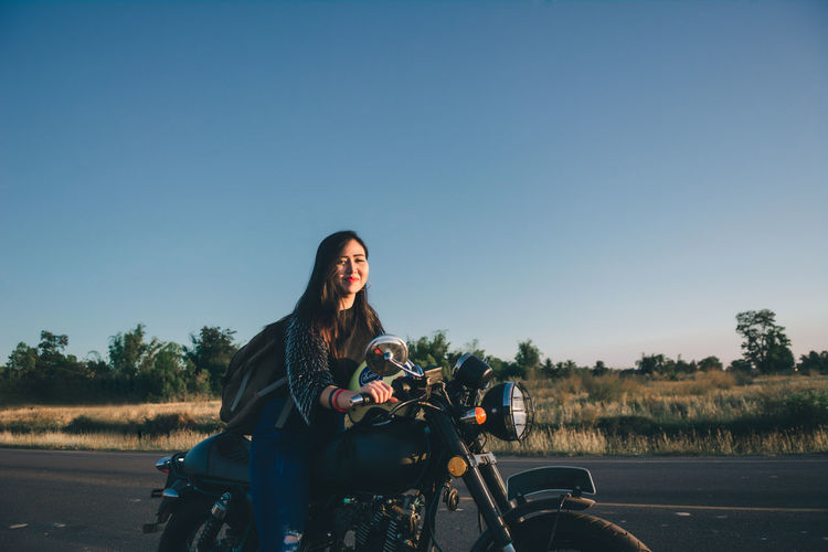 Portrait of young woman sitting on motorcycle against clear sky