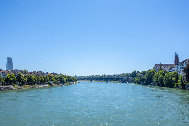 River passing through city against clear blue sky