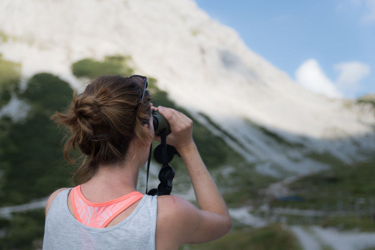 Rear View Of Woman Looking Through Binoculars Against Mountains