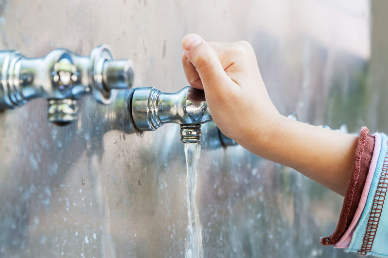 Close-up of hand holding faucet with running water