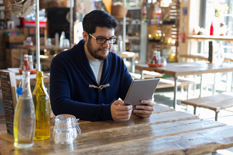 Blackandwhite Browsing The Internet Casual Clothing Focus On Foreground Freshness Indulgence Leisure Activity Lifestyles Person Refreshment Restaurant Sitting Smartphone Table Tablet People And Places