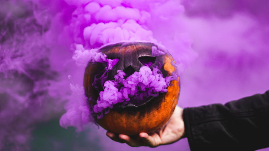 Close-up of person holding jack o lantern emitting smoke