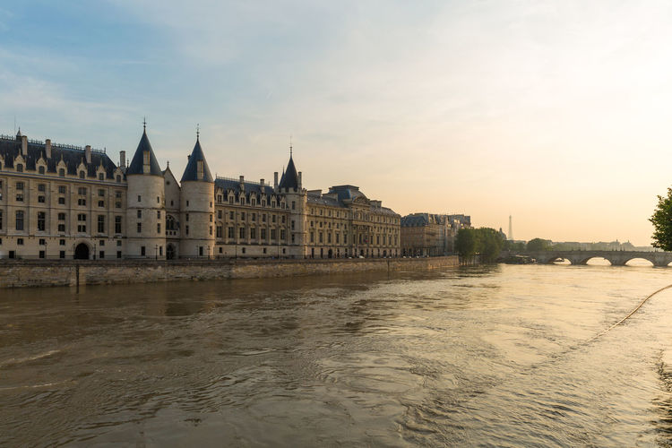 Conciergerie by river in city against sky during sunset