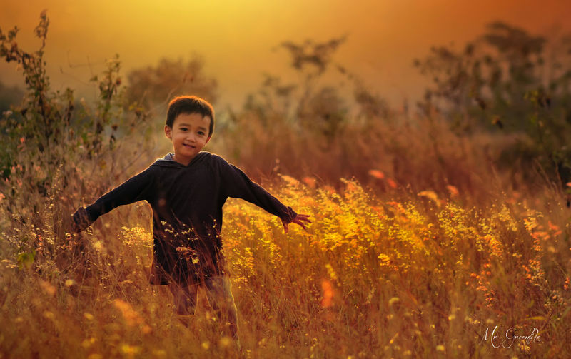 Portrait of smiling boy with arms outstretched standing amidst plants on field during sunset