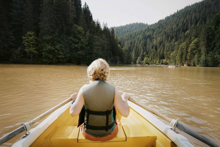 Rear view of woman rowing boat in river against mountains