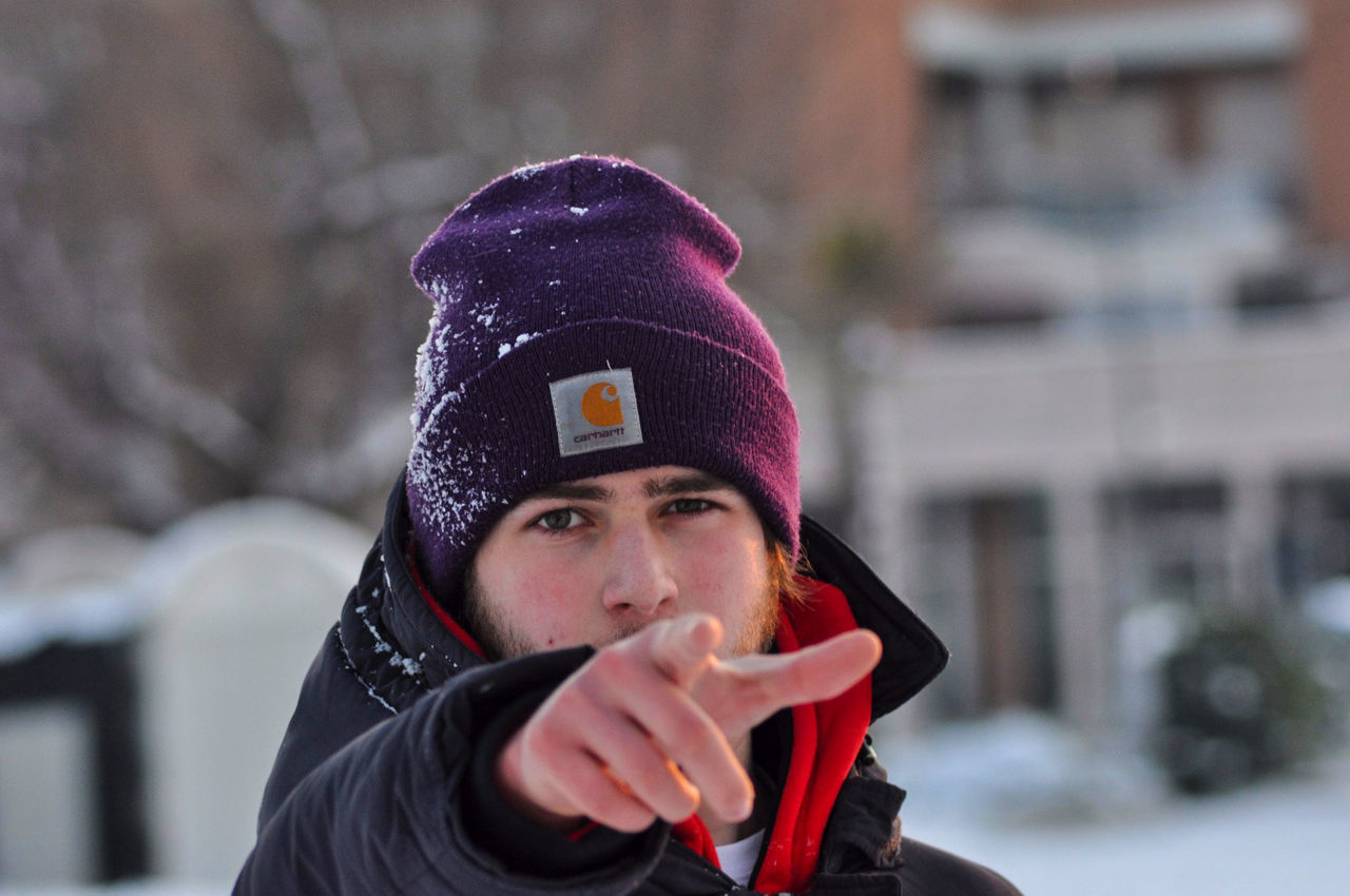 one person, winter, focus on foreground, wireless technology, real people, lifestyles, cold temperature, front view, outdoors, communication, leisure activity, knit hat, connection, warm clothing, technology, day, young adult, headshot, scarf, young women, portable information device, cap, snow, close-up, people