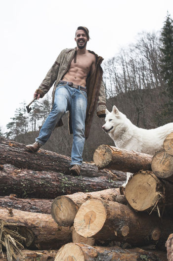 Portrait of young man standing with dog on logs of wood in forest against sky