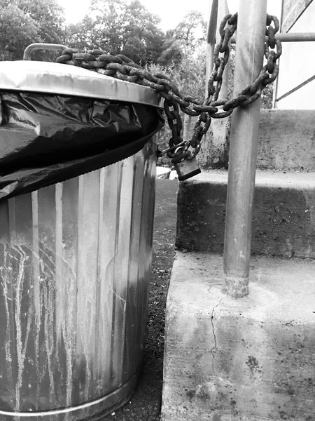 Dirty black and white trash can chained to exterior staircase handrail. Lifestyles Locked Up Chain Park Waste Management Stairs Cement Outdoor Outside nNo PeopledDaybBuilt StructureaArchitectureoOutdoorscClose-upnNaturetTrash Can