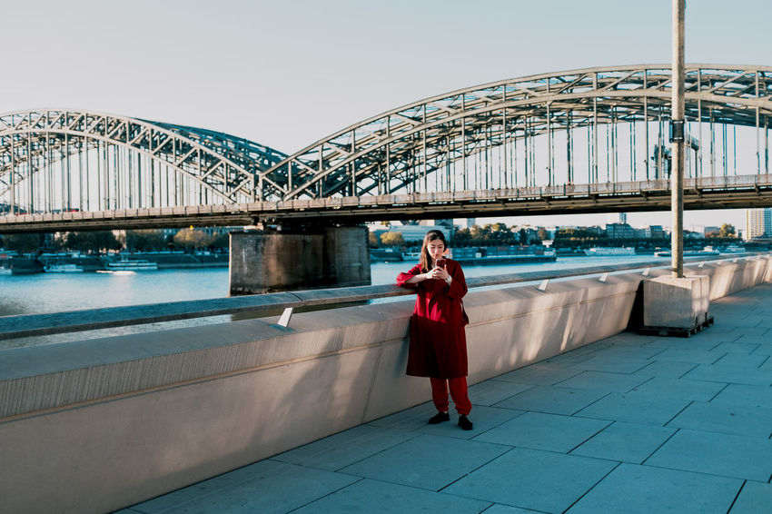 Bridge View in Cologne Adult Architecture Beautiful Woman Bridge Bridge - Man Made Structure Built Structure Clothing Connection Fashion Front View Full Length Lifestyles One Person Real People Sky Standing Twodayscologne Water Women Young Adult Young Women