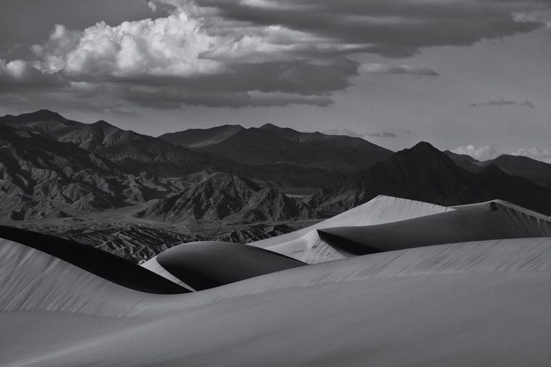 Idyllic shot of sand dunes and mountains in desert against sky