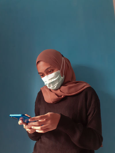 Midsection of young woman holding smart phone against blue background