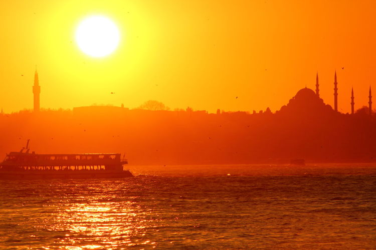 Passenger crafts sailing in strait by silhouette suleymaniye mosque against sky during sunset