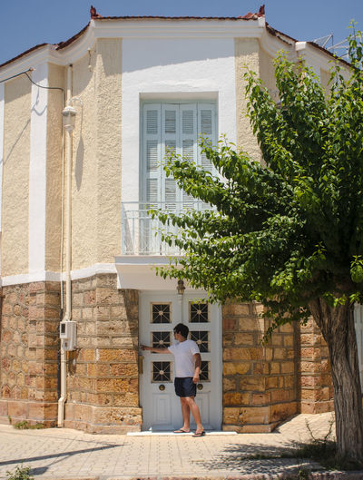 Rear view of man standing outside house