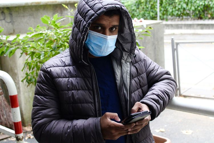 Portrait of man wearing mask using mobile phone standing outdoors