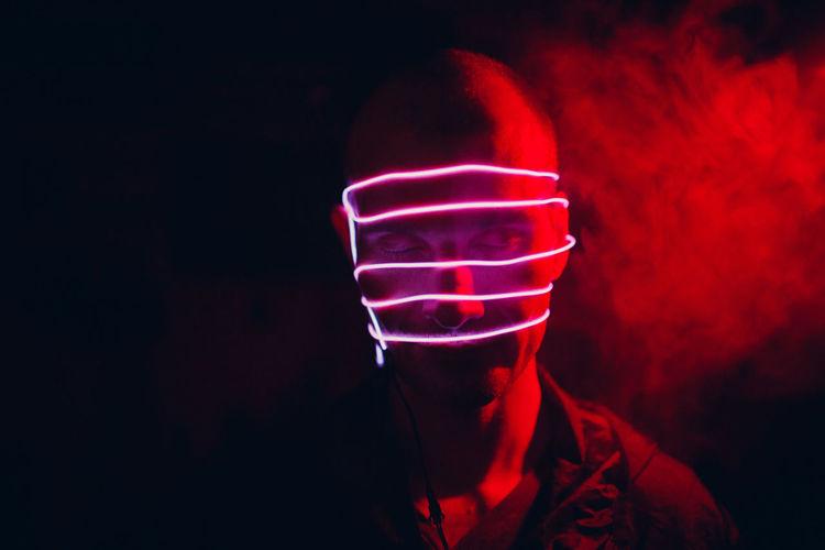Close-up of hand holding illuminated light against black background