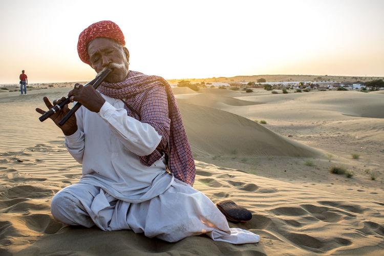 Full length of man sitting on rock in desert against sky