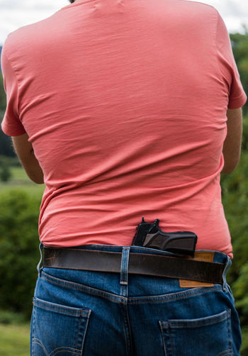 Rear view of man standing outdoors with a gun