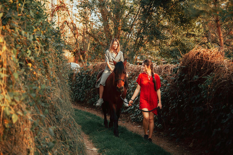 Young women sitting on horse with walking friend amidst trees