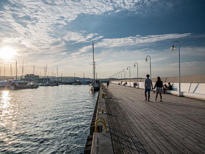 People on pier at sea against sky