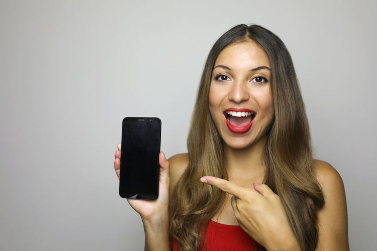 Close-up portrait of cheerful young woman showing mobile phone against gray background
