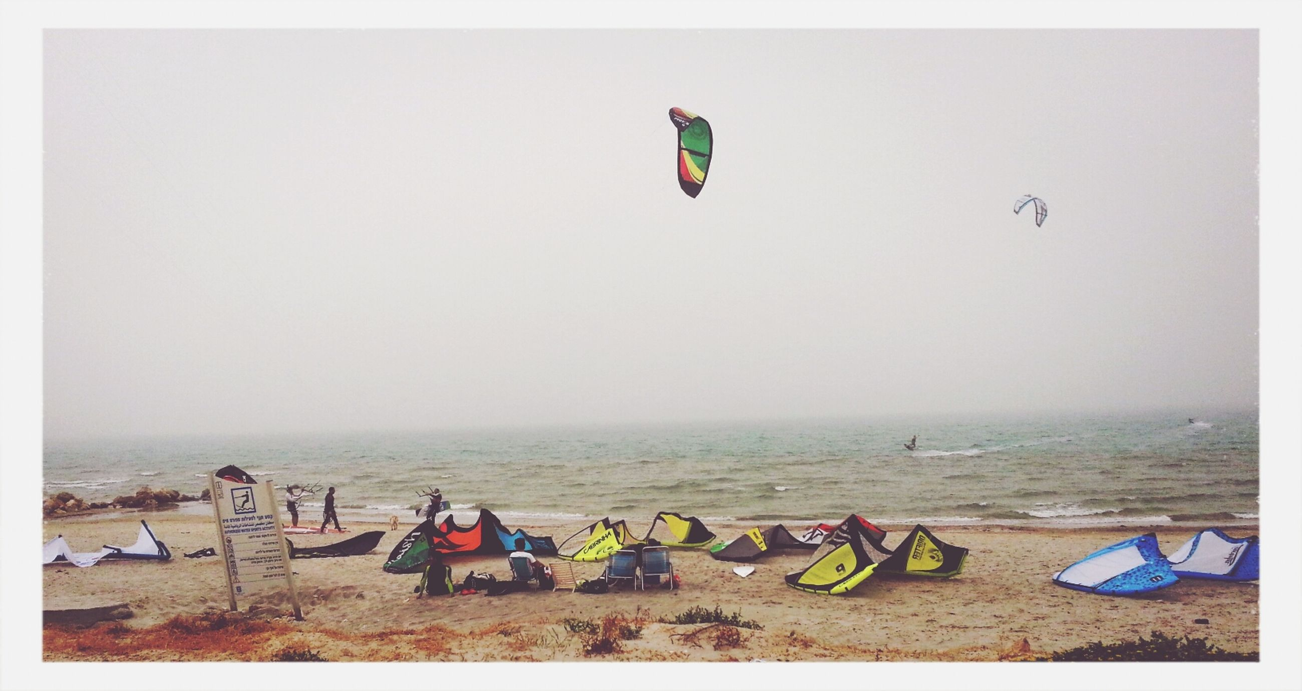 beach, sea, flying, clear sky, sand, horizon over water, copy space, shore, parachute, sky, multi colored, transportation, vacations, mid-air, flag, water, day, beach umbrella, transfer print, auto post production filter