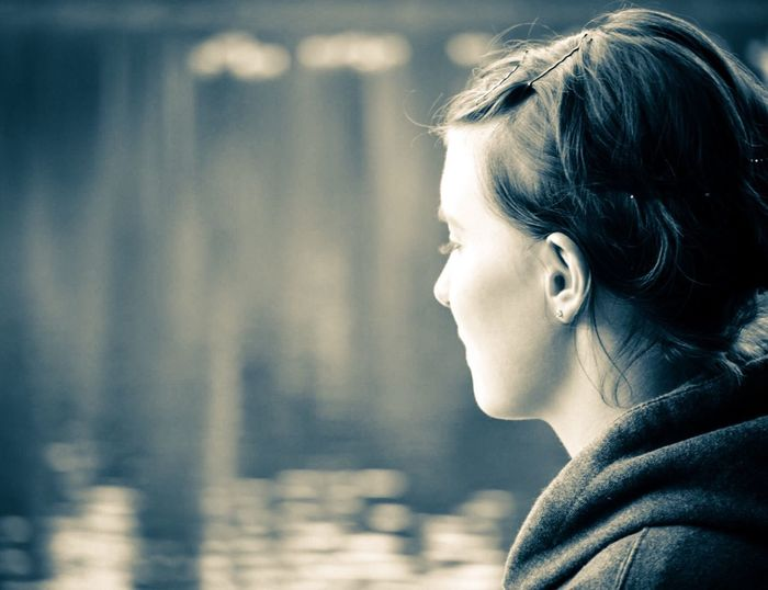 Close-Up Of Thoughtful Woman With Lake In Background