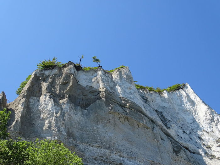 Low angle view of rock against clear blue sky