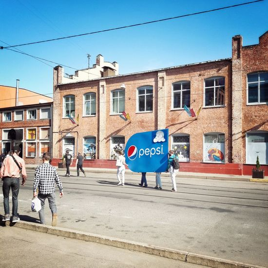 Group of people bears an advertising poster with a famous brand. Minsk Minskcity  Belarus Vulicabrasil Streetart Graffiti Streetphotography Famous Pepsi Drink Dog Blue Day One Animal Architecture Sky City Adult