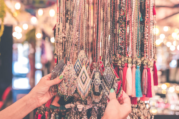 Cropped hands of woman holding multi colored necklaces for sale in store