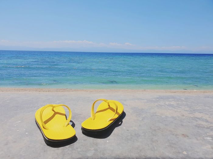 High angle view of shoes on beach against sea